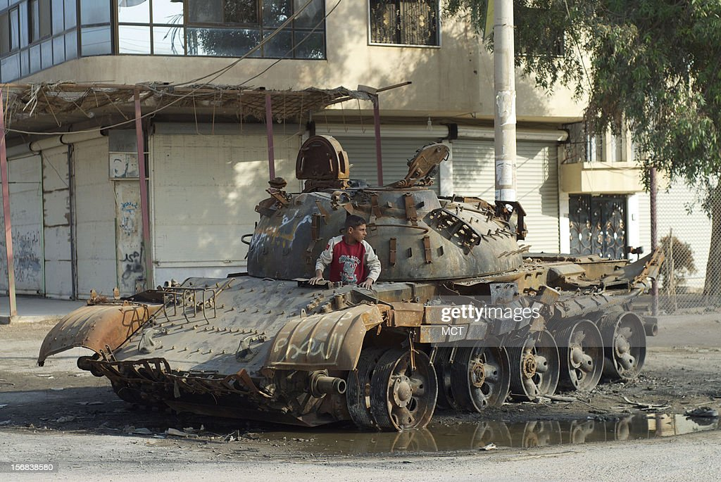 A child plays on a destroyed Syrian army tank in Mayadeen, Syria, where rebels forced the Syrian army to withdraw from a artillery base on Thursday, November 22, 2012.