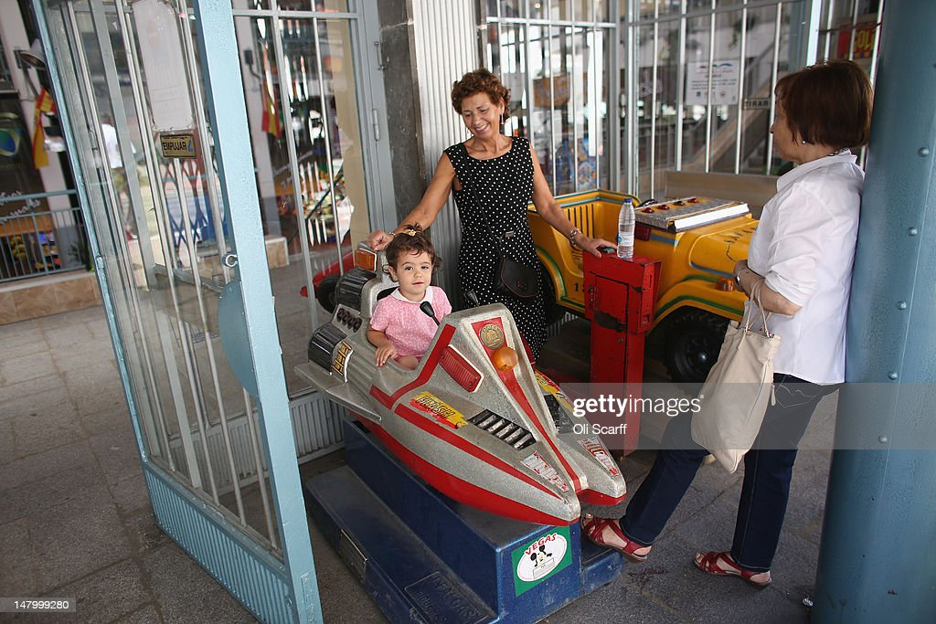 A child plays on a ride outside an indoor market near the Plaza de Cascorro on July 7, 2012 in Madrid, Spain. Despite having the fourth largest economy in the Eurozone, the economic situation in Spain remains troubled with their unemployment rate the highest of any Eurozone country. Spain is currently administering billions of euros of spending cuts and tax increases in a bid to manage its national debt. Spain also has access to loans of up to 100 billion euros from the European Financial Stability Facility which will be used to rescue the country's banks that have been badly affected by a crash in property prices.