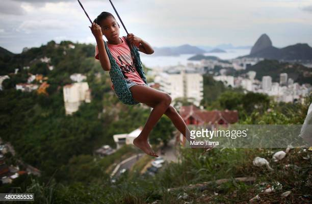 A child plays on a swing in the Prazeres pacified favela community on March 22 2014 in Rio de Janeiro Brazil The favela was previously controlled by...