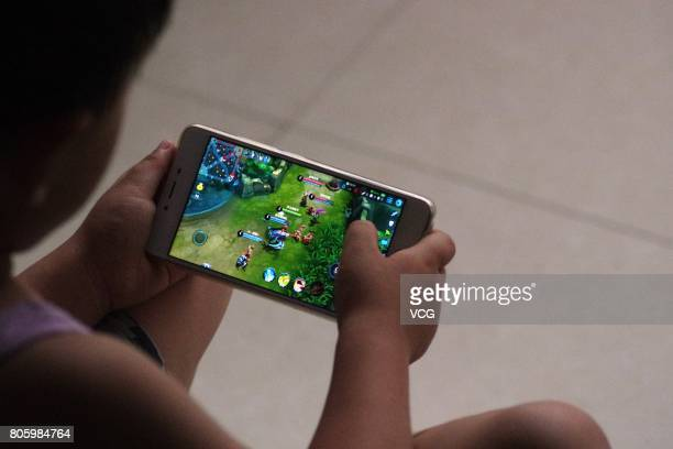 A child plays online game 'Honor of Kings' on July 2 2017 in Dezhou Shandong Province of China China's Tencent will restrict each account's daily...