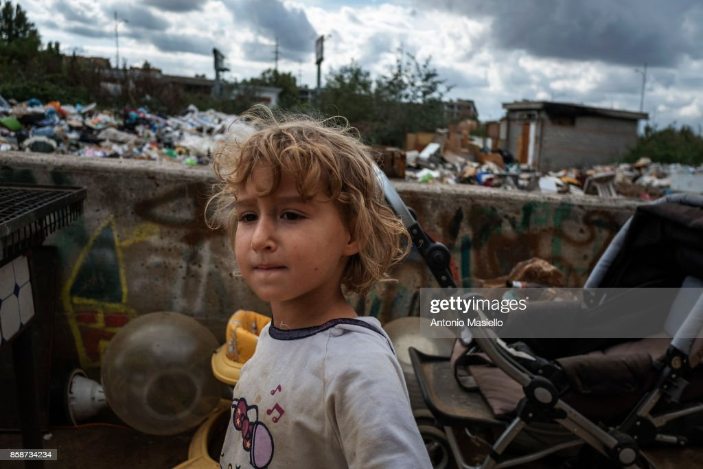 A child plays outside an occupied building on October 4, 2017 in Rome, Italy.For the last 5 years, hundreds of people, including Italians, Roma and refugees, including around 35 children, have lived in an occupied building on the suburbs of Rome without electricity or a toilet and surrounded by refuse.