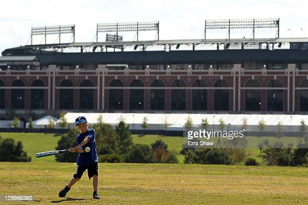 A child plays outside with Rangers Ballpark in Arlington in the background prior to Game Three of the MLB World Series between the St Louis Cardinals...