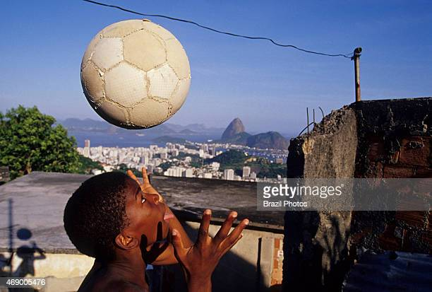 Child plays soccer in a Rio de Janeiro favela black boy have fun with his ball Sugar Loaf mountain in background