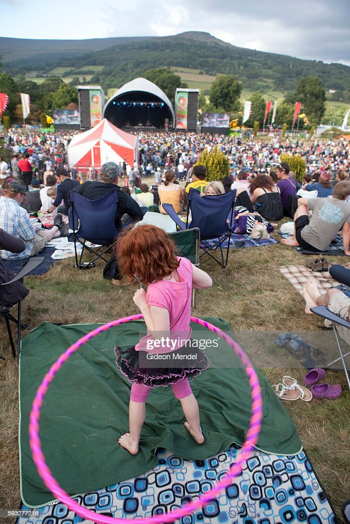 A child plays with a hula hoop while the audience enjoys a performance by James Blake on the main stage of the Green Man Festival during a...