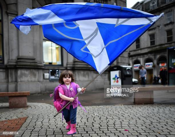 A child plays with a proindependence 'Yes' flag on the streets of Aberdeen in Scotland on September 15 ahead of the referendum on Scotland's...