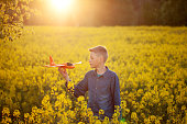 Kid plays with a toy airplane in the sunset and dreams of journey in summer day.