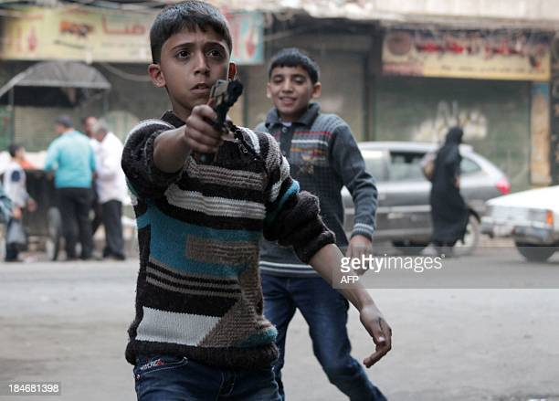 A child plays with a toy gun in the Bustan alQasr neighbourhood of the northern Syrian city of Aleppo on October 15 2013 The United States said there...