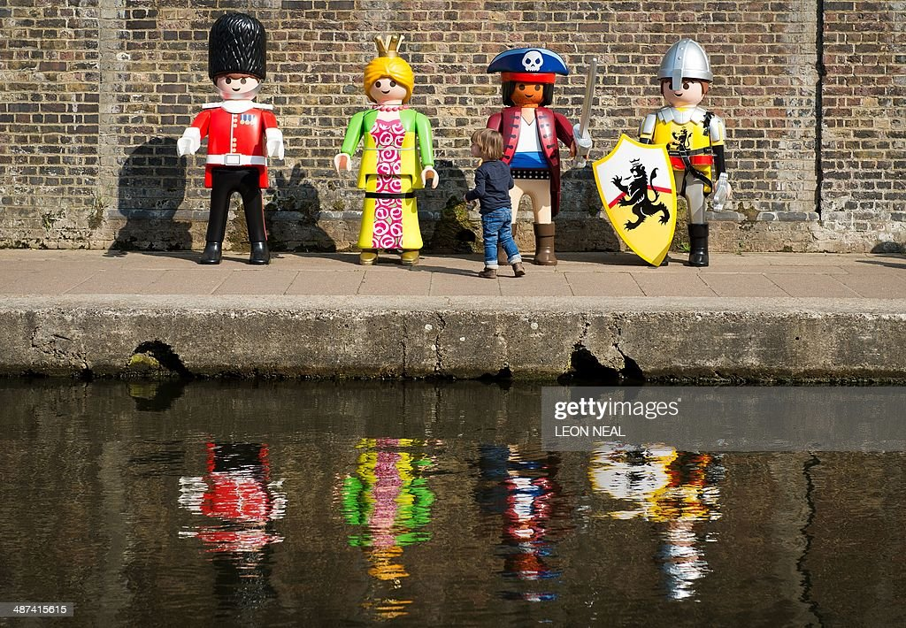 A child plays with giant Playmobil figures during a photocall on the canalside at Camden in north London, on April 30, 2014, as the toy company celebrates its 40th anniversary.