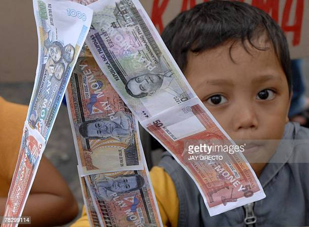 A child plays with Philipine peso 'notes' during a protest in Manila 06 December 2007 The peso hit a fresh sevenandahalfyear high of 4185 pesos...