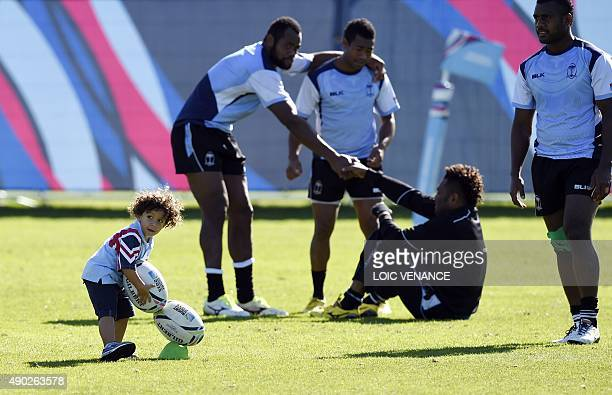 A child plays with rugby balls during a Fiji training session on September 27 2015 in Swansea during the 2015 Rugby World Cup AFP PHOTO / LOIC...