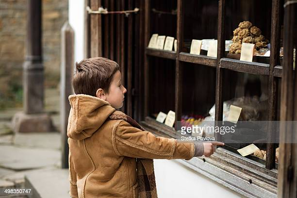 Child pointing a finger at a shop window
