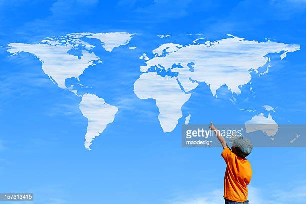 Child pointing at a sky with world map as clouds
