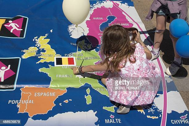 A child points to a map of Europe as youths and adults participate in putting together a puzzle made up of colorful pieces representing different...
