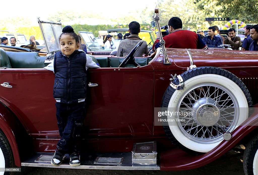 A child pose on a vintage car during the '21 Gun Salute Vintage Rally' on December 9, 2012 in New Delhi, India.