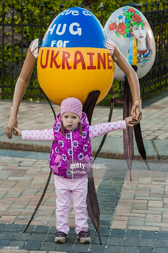 Child poses for a photo under a painted Easter egg in the streets of Kiev, Ukraine. on 30 April 2016.