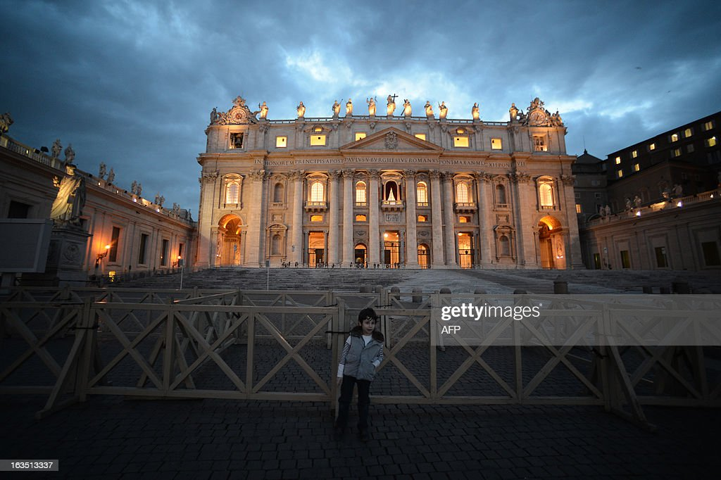 A child poses in front of the St Peter's basilica at sunset on the eve of the conclave on March 11, 2013 at the Vatican. Catholic cardinals had a final day of jockeying for position the same day before shutting themselves into the Sistine Chapel to elect a new pope after Benedict XVI's shock resignation, with an Italian and a Brazilian who both head powerful archdioceses among the top contenders. AFP PHOTO / FILIPPO MONTEFORTE