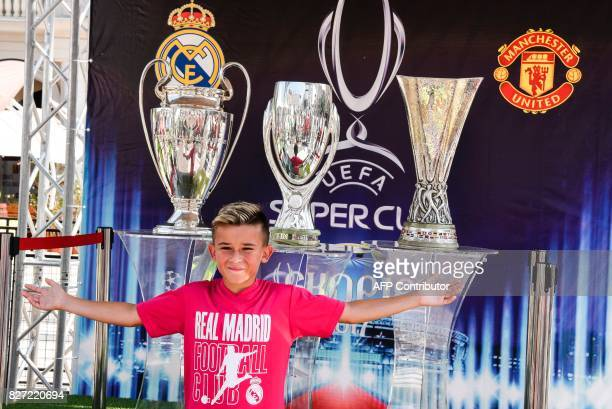 A child poses in front of trophies at the Uefa Super Cup fan zone in Skopje on August 7 one day ahead of UEFA Super Cup match between Real Madrid and...