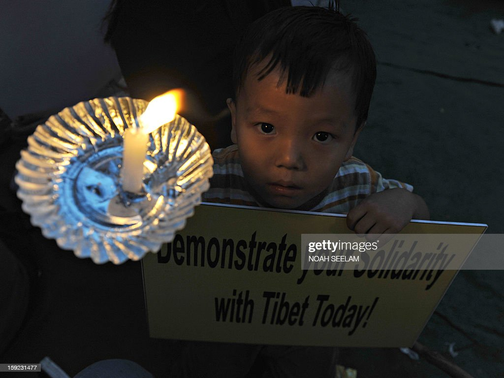 A child poses with a candle and placard as members of the Regional Tibetan Youth Congress (RTYC) take part in a candlelight vigil in Hyderabad on January 10, 2013, in protest at the continuing deterioration of their countrymen's human rights. The central Tibetan administration and Tibetans the world over will observe the year 2013 as the year of 'Solidarity with Tibet'. AFP PHOTO/Noah SEELAM
