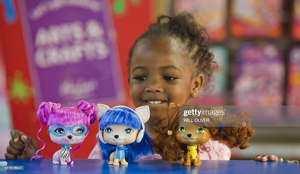 A child poses with a set of VIP Pets during a photocall at Hmleys toy shop in London on June 27, 2013. Hamleys unveiled the 'must have' toys for Christmas 2013@ at the companys' flagship Regent Street store in London. AFP PHOTO/WILL OLIVER