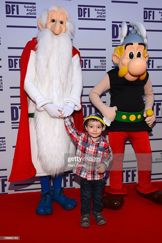 A child poses with Getafix and Asterix at the 'Asterix and Obelix 3D' Premiere during the 2012 Doha Tribeca Film Festival at o n November 23, 2012 in Doha, Qatar.