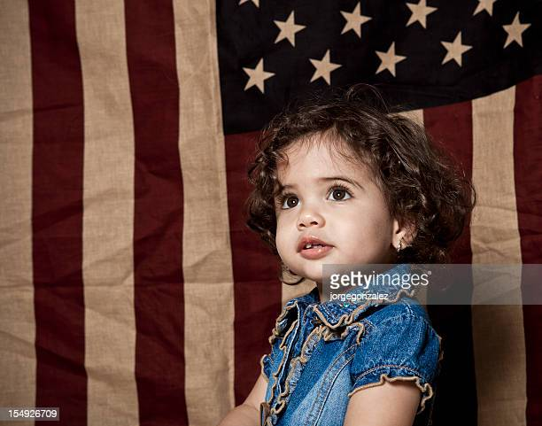 Child posing in front of american flag
