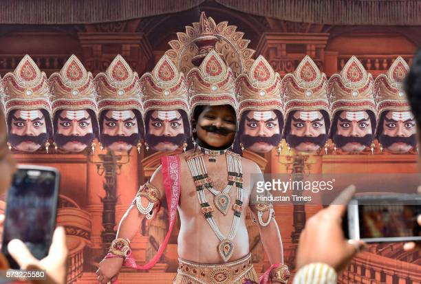A child posing with the cutout of Ravana during Makkala Hanna Children Festival at Cubbon Park on November 12 2017 in Bengaluru India Karnataka...
