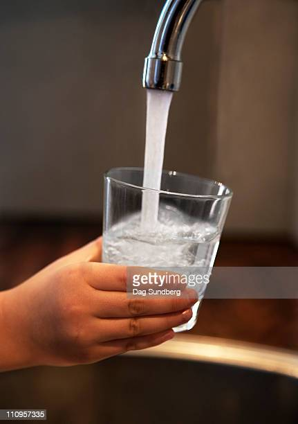Child pouring fresh water in glass