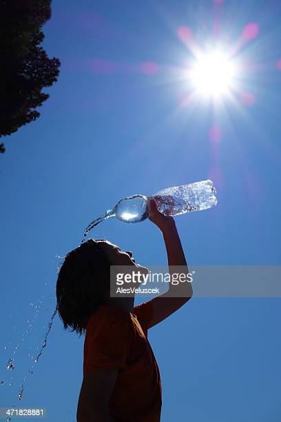 Child pouring water on self silhouetted on blue