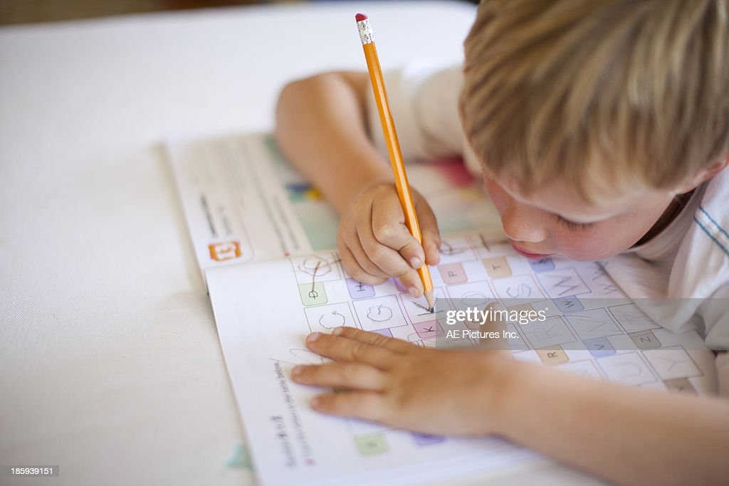 Child practices writing letters : Stock Photo