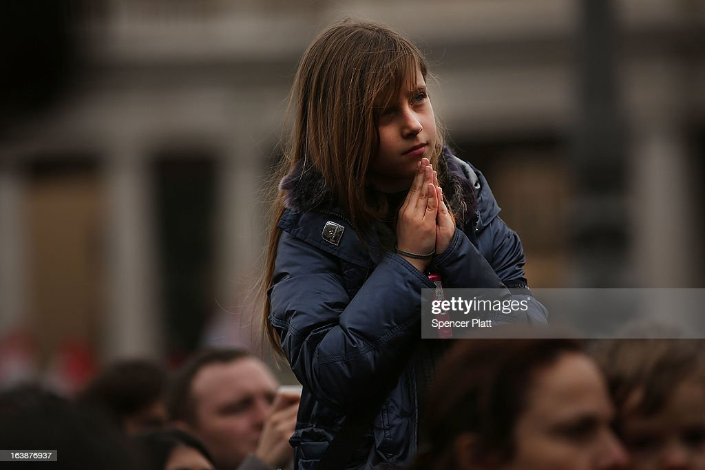 A child prays as Pope Francis appears in the window of his private residence in St Peter's Square to give his first Angelus blessing on March 17, 2013 in Vatican City, Vatican. The Vatican is preparing for the inauguration of Pope Francis on March 19, 2013 in St Peter's Square.