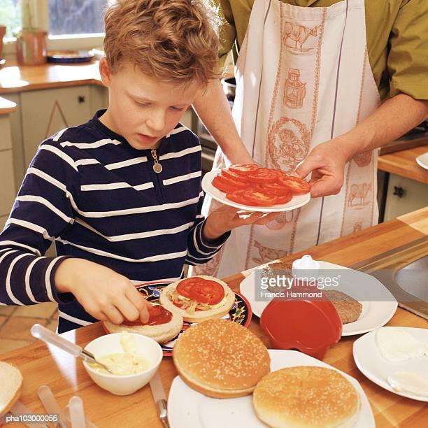 Child preparing hamburgers with sliced tomatoes