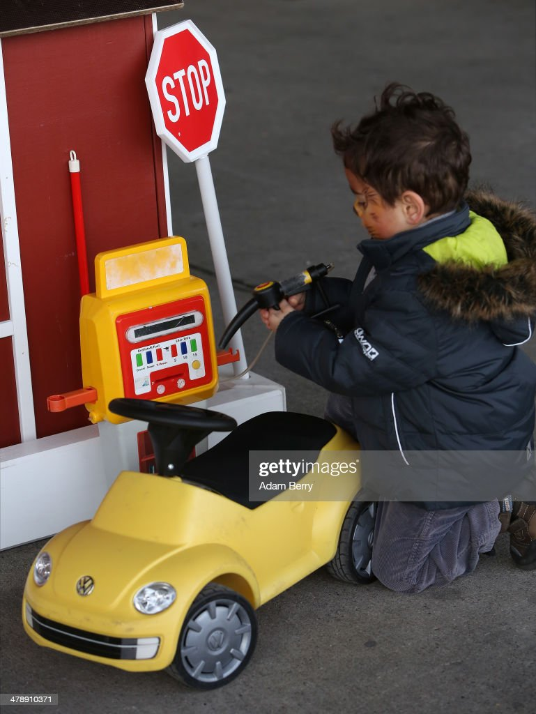 A child pretends to put fuel into a toy Volkswagen Beetle at the Electric Mobility Week (e-Mobilitaetswochen), a public Volkswagen (VW) event at the former Tempelhof airport, on March 15, 2014 in Berlin, Germany. The event was designed to promote the company's e-Golf und e-up! automobiles, as well as its other alternative energy powered vehicles.
