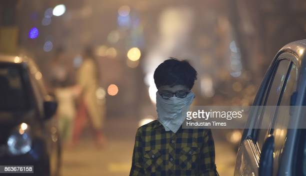 A child protects her face amid heavy smog due to bursting firecrackers despite the ban imposed by the Supreme Court of India to keep a check on air...