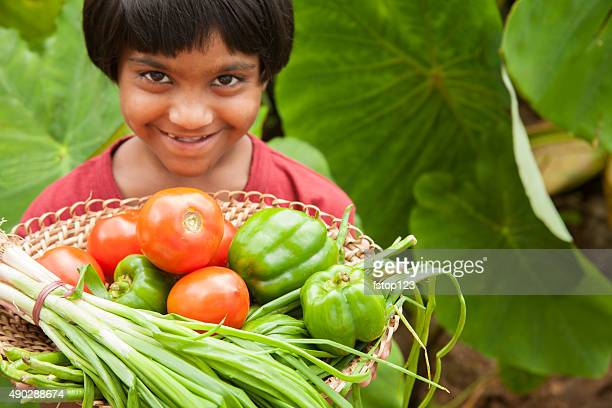 Child proudly harvests vegetables from community garden.