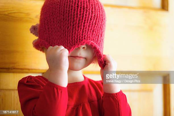 A Child Pulling A Hat Over Her Eyes