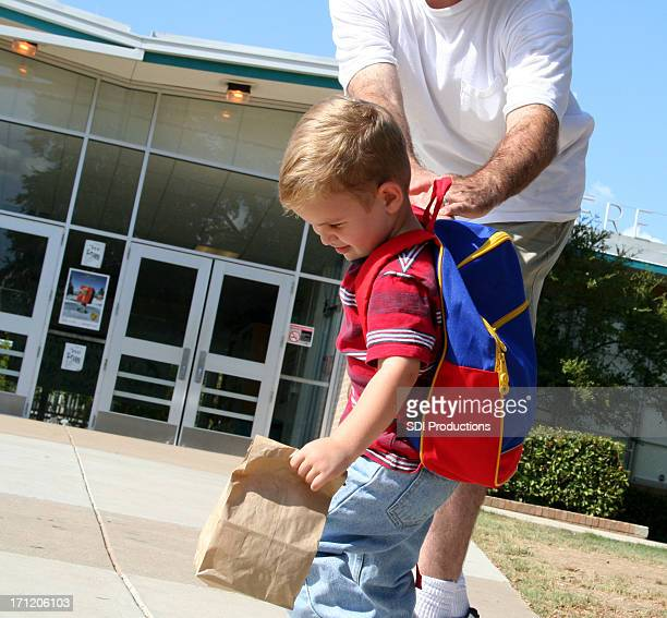 Child pulling away from father at school building