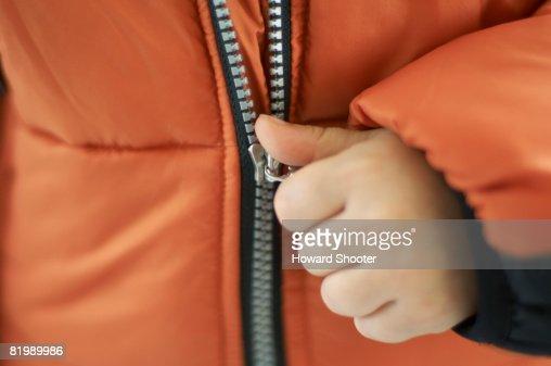 Child pulling zip on orange jacket, close up