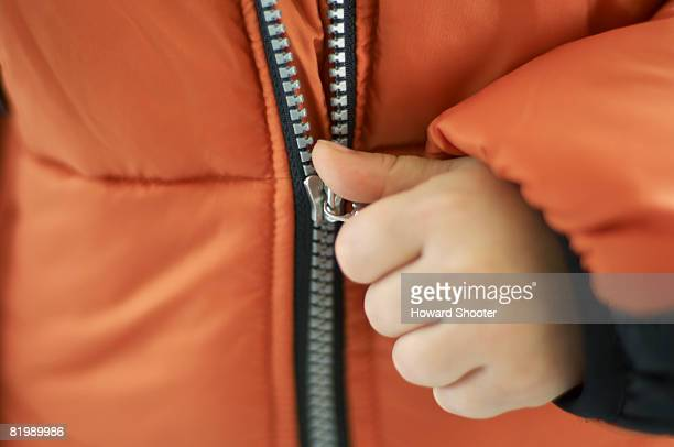 Child pulling zip on orange jacket, close up