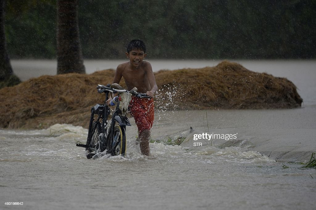 A child pushes his bicycle as he crosses a flooded street in Ineangan Bambang Nueva Viscaya after the Magat river swelled caused by typhoon Koppu's...
