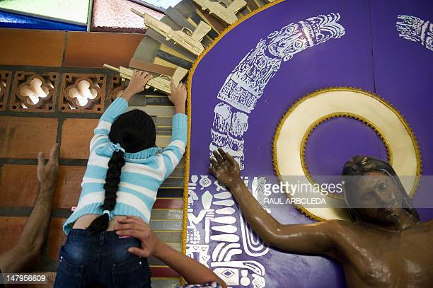 A child puts a fiberglass gun to complete the work Cristo Moreno by Peruvian artist Cristina Planas Toledo during the opening of the first mausoleum...