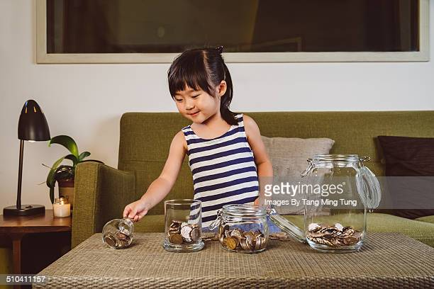 Child putting coins into glass jars at home