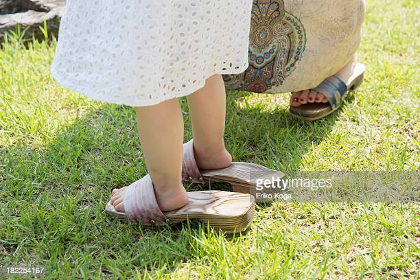 Child Putting on Adult's Shoes