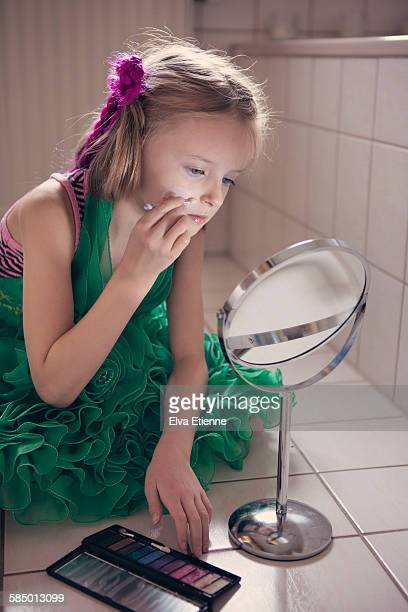 Child (8-9) putting on make-up in bathroom