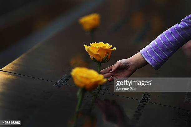 A child reaches out to touch a flower adorning the 9/11 Memorial on the name of a veteran killed on September 11 2001 for Veterans Day on November 11...