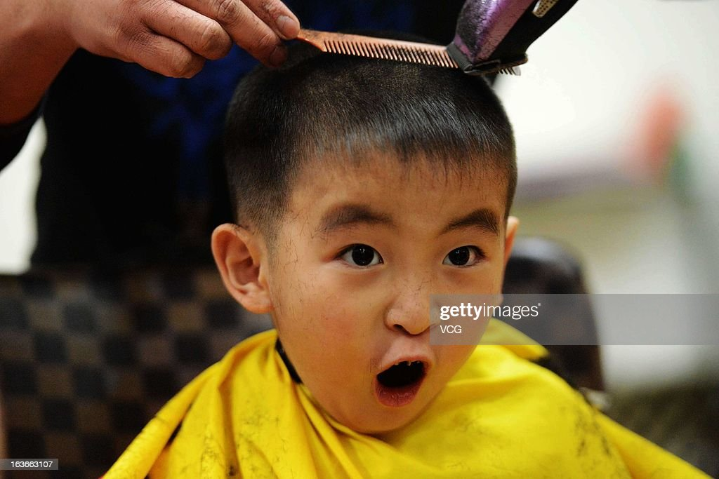A child reacts as he gets a haircut at a barbershop during the traditional festival known as Dragon Head Raising Day on March 13, 2013 in Qingdao, China. Dragon Head Raising Day is celebrated on the second day of the second lunar month in China during which the traditional custom of getting a haircut is believed to bring good luck.