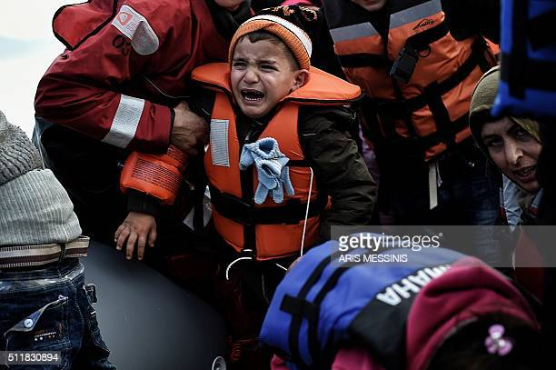 TOPSHOT A child reacts as refugees and migrants disembark a rubber boat upon arrival at the northern island of Lesbos after crossing the Aegean sea...