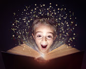 Child reading a magicical story  book with letters leaping off the page