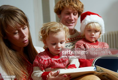Child reading book on mother's lap at Christmas. : Stock Photo