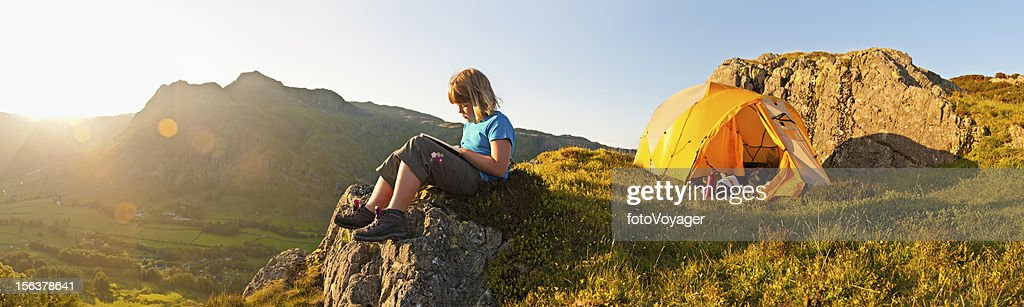Child reading book summer sunset mountain camping panorama