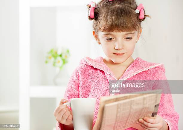Child reading newspapers and drink tea